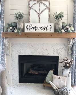 fall-fireplace-with-buffalo-check-and-sage-green-pumpkins-for-a-farmhouse-look.-Shiplap-and-herringbone-tile-on-the-fireplace-